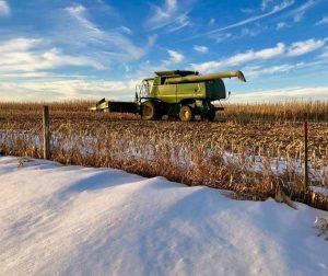 John Deere combine in a snowy field